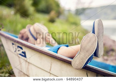 Boy Lying In Old Boat In The Lake Coast Close Up Image