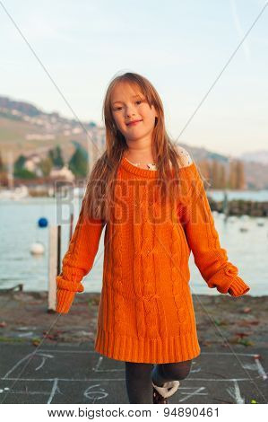 Portrait of a cute little girl playing outdoors, wearing bright big orange mother's pullover