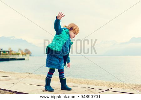 Outdoor portrait of adorable toddler girl of 2 years old, wearing green waistcoat, denim skirt and b