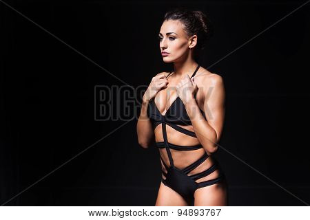 Sexy young woman with perfect body wearing black lingerie. Beautiful fashion model posing in dramati