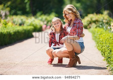 Portrait of a beautiful mother and daughter in the summer park