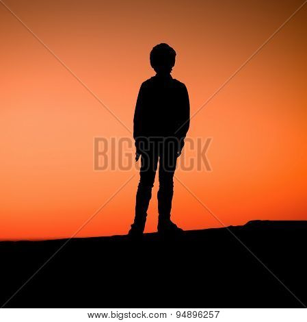 Young boy is standing on pier enjoying the sunset. Silhouette of a kid
