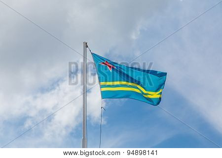 Flag Of Aruba Under Clouds