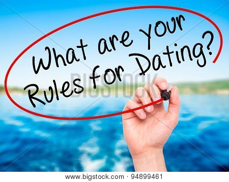 Man Hand writing What are your Rules for Dating? with black marker on visual screen.