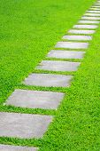 stock photo of stepping stones  - pathway with rock and grass in a garden - JPG