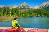 stock photo of mountain-high  - Young man sitting on red boat at the pier mountain lake in the background of the high peaks of the mountains - JPG