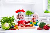 picture of vegetarian meal  - Kids cooking fresh vegetable salad in a white kitchen - JPG