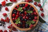foto of blackberries  - Salad of cherry raspberry currant and blackberry in a wooden bowl on the table close - JPG