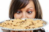 image of stare  - Young woman holding staring at a tray with homemade chocolate cookies - JPG
