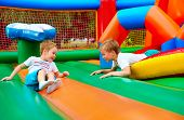foto of daycare  - happy kids having fun on inflatable attraction playground - JPG