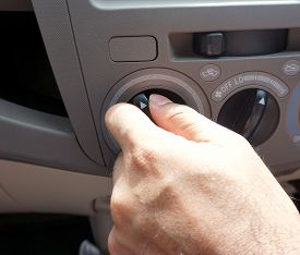 stock photo of designated driver  - Male driver turning car air conditioner knob - JPG