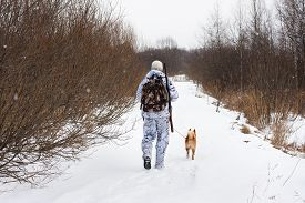 image of hunter  - hunter with dog walking on the winter road - JPG