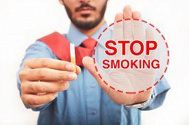 stock photo of smoke  - Men showing stop smoking sign with a cigarette half broken - JPG