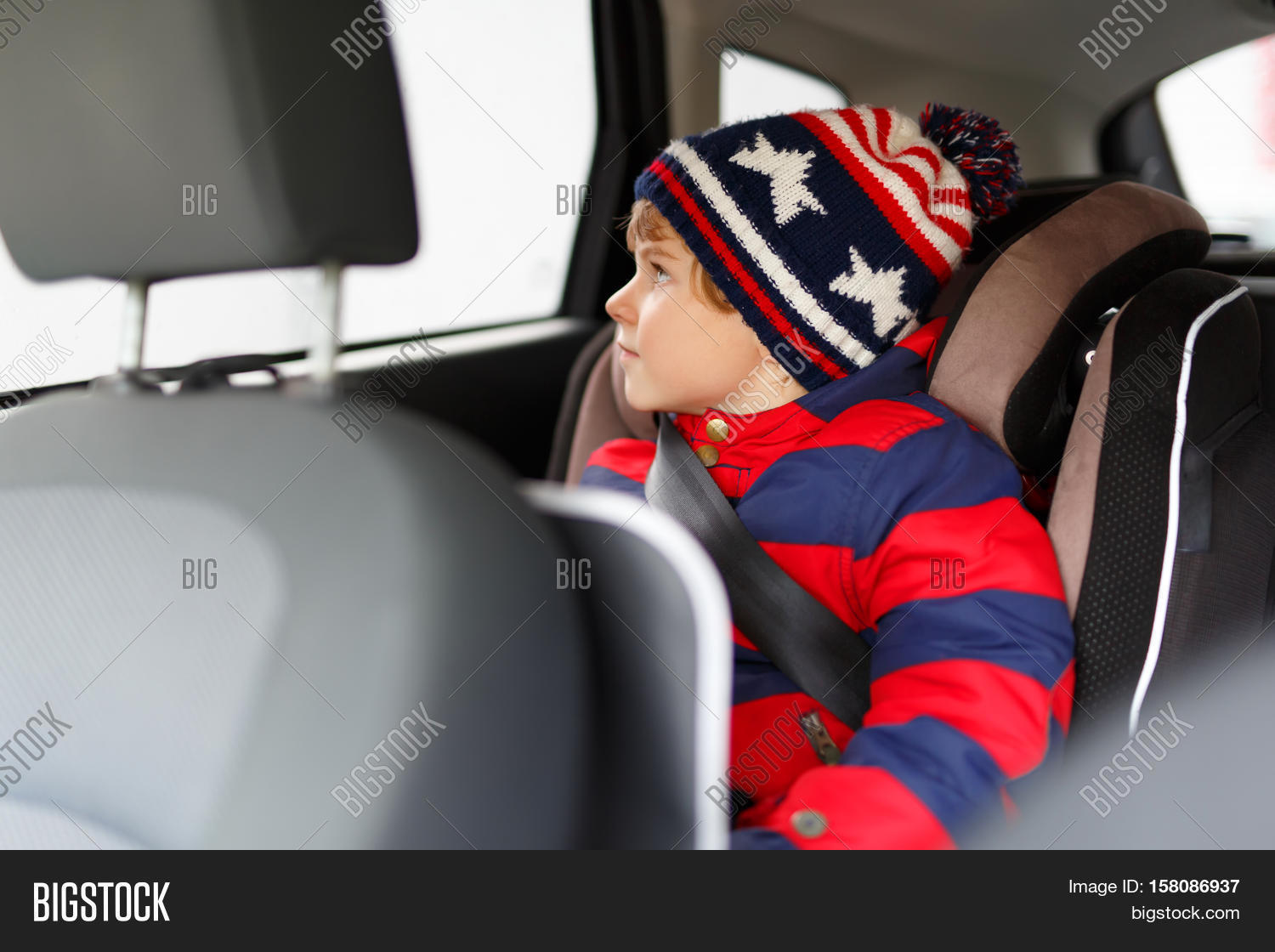 adorable cute preschool kid boy sitting in car in winter clothes little child in safety