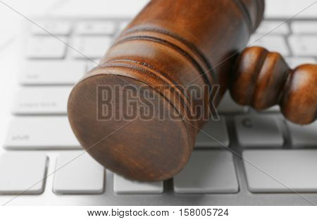 Wooden judge's gavel on computer keyboard, closeup