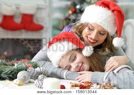 Portrait of mother and preteen daughter preparing for Christmas, girl fell asleep