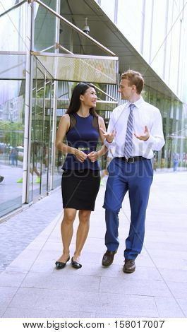 Professionally dressed man and woman talking business