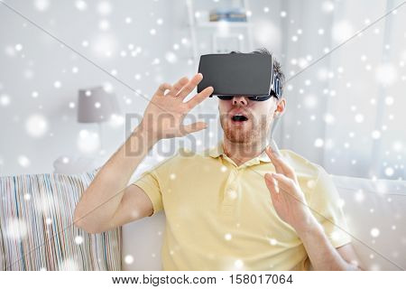 technology, augmented reality, gaming, entertainment and people concept - amazed young man with virtual headset or 3d glasses playing game over snow