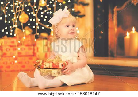 Christmas Happy Child Little Girl With Gift Box Near Christmas Tree And Fireplace At Home