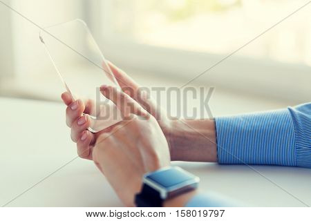 business, technology and people concept - close up of woman hand holding and showing transparent smart phone and watch at office