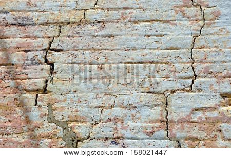 Old cracked rendered wall from historic building with exposed brick and mortar and peeling paint. Grunge texture background with copy space.