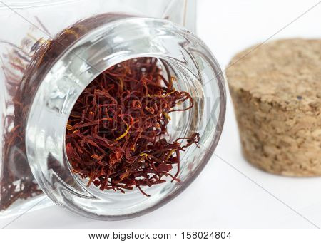 close up image of Saffron in a thick glass jar with a cork stopper in the background copy space to the right