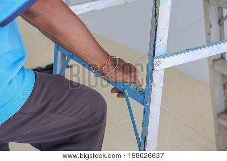 man hand Close up climbing ladder .