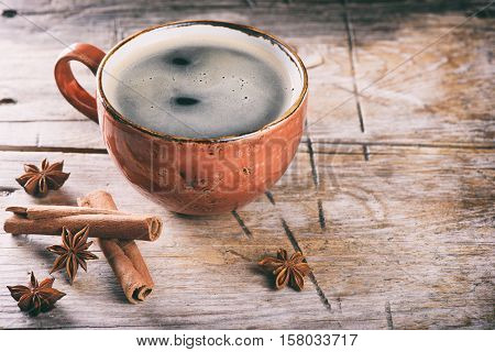 Coffee Cup Cinnamon Sticks On A Wooden Table.