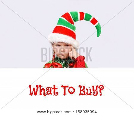 Girl in suit of Christmas elf with the white banner thinking what to buy. Background for your Merry Christmas and Happy New Year projects.