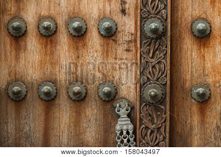 traditional arab zanzibar wooden door and doorway ornately carved and decorated with brass fittings
