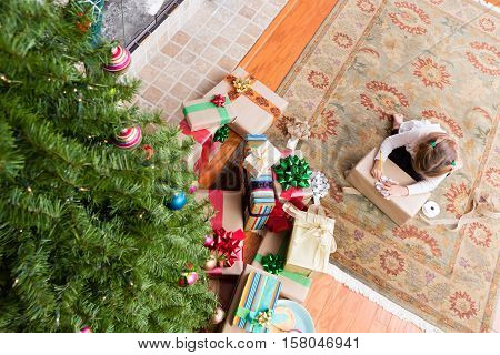 Young Girl Wrapping Her Family Christmas Presents