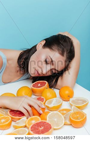 Attractive young woman sleeping on the table with oranges and grapefruits over blue background