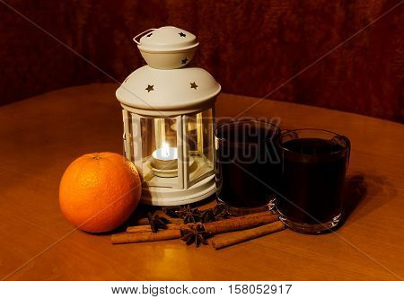 Christmas lantern and mulled wine on wooden table