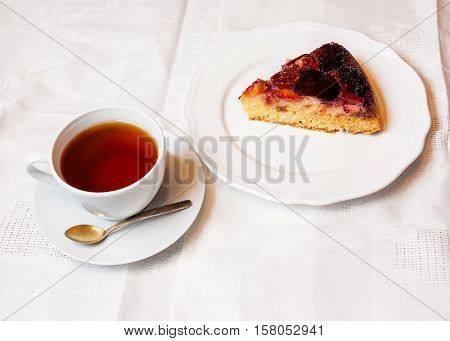 Plum cake and cup of tea on table
