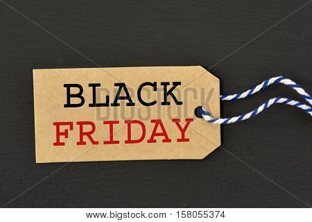 a brown paper label with the text black friday written in it against a dark gray background