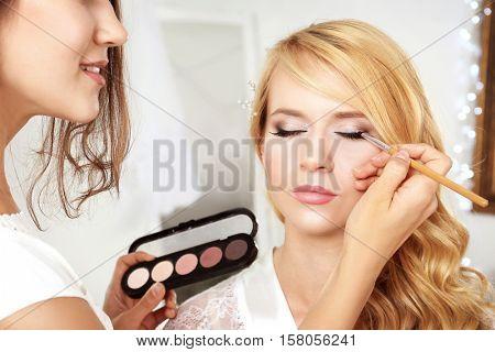 Artist applying eye shadow on beautiful woman eyes