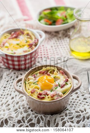 Baked pasta spaghetti carbonara with egg yolk cheese and bacon served with salad