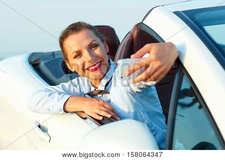 Young smiling woman making self portrait sitting in the cabriolet