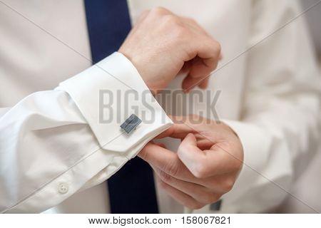 Elegant young fashion man fixing his cufflinks, closeup