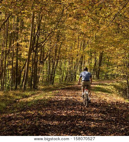 Senior adult caucasian man cycling away down a leaf covered Deckers Creek Rail trail near Morgantown in West Virginia