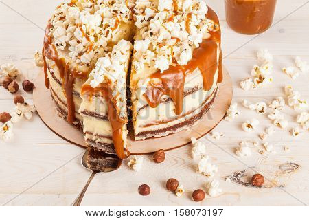 Homemade cake with hazelnuts and salty caramel with vanilla - hazel shortcakes and delicate hazelnut cream, decorated with salty popcorn. Cut a piece of cake on the blade