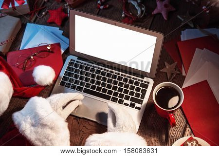 Santa Claus working on computer. Open laptop with white screen concept