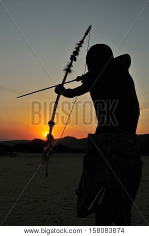 Man from Hadza tribe hunting with traditional bow and arrow as they did thousands of years ago. Hadza tribe is an ethnic group in north Tanzania