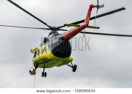 Tyumen, Russia - August 23, 2008: On visit at UTair airshow in Plehanovo heliport. Rescuer is landed from MI-8 helicopter by rope