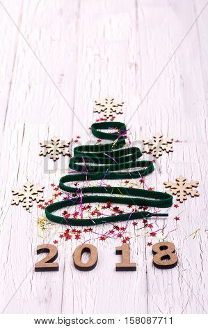 Christmas Tree Made Of Ribbons And Wooden Snowflakes Lies On White Table Over Wooden Number 2018