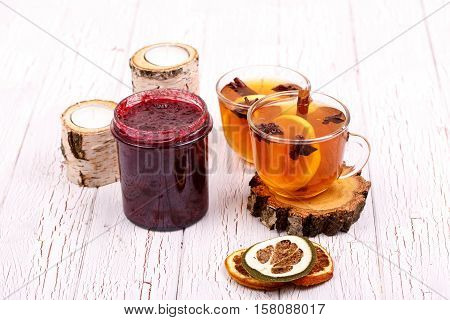 Cup Of Tea With Cinnamon, Lemon And Other Seasonings Stands On White Table Between Candles, Jelly An