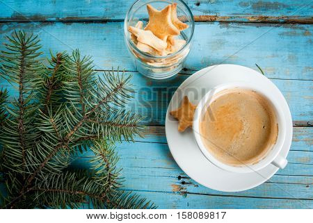 Cup of coffee with the sprigs of a christmas tree and cookies in the shape of stars. On a blue wooden table top view copy space