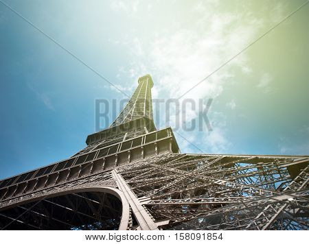 Majestic Eiffel Tower in Paris shot from Champs de Mars against a blue sky shoto from unusual angle - point of view of a pedestrian tourist admiring Paris