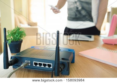 closeup of a wireless router and a young man using a smartphone on living room at home with a window in the background