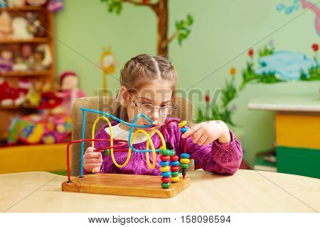 Cute Little Girl Playing With Developing Toy In Kindergarten For Kids With Special Needs